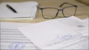 Επαγγελματικά επιχειρησιακά έγγραφα και έγγραφα, γυαλιά, μάνδρα και copybook απόθεμα βίντεο