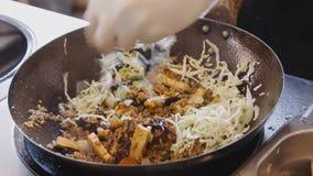 Επαγγελματικά τηγανίζοντας λαχανικά και ρύζι μαγείρων στο φεστιβάλ τροφίμων οδών Διαδικασία κοντά επάνω φιλμ μικρού μήκους