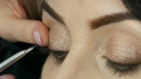 Επαγγελματική έναρξη καλλιτεχνών makeup για να κολλήσει τα ψεύτικα eyelashes στα μπλε μάτια μιας ενήλικης μέσης ηλικίας στενής επ απόθεμα βίντεο