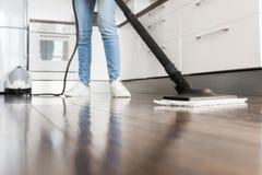 Επαγγελματική εγχώρια καθαρίζοντας υπηρεσία Η γυναίκα πλένει το πάτωμα με μια σφουγγαρίστρα ατμού στοκ εικόνες