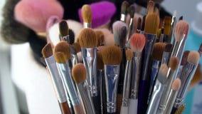 Επαγγελματική εξάρτηση βουρτσών καλλυντικών makeup στην κίνηση φιλμ μικρού μήκους