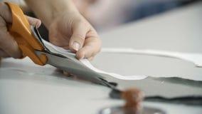 Επαγγελματική μοδίστρα, seamstress τέμνον ύφασμα με το ψαλίδι στο ράψιμο του στούντιο Έννοια μόδας και προσαρμογής φιλμ μικρού μήκους