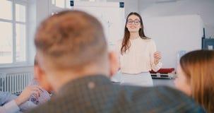 Επαγγελματική νέα θετική επιχειρησιακή ειδική γυναίκα στα γυαλιά που μιλά στην ευτυχή multiethnic ομάδα στον κύκλο μαθημάτων κατά φιλμ μικρού μήκους