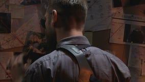 Επαγγελματική σπόλα που εξετάζει τον πίνακα εγκλήματος και που καπνίζει το πούρο, που ψάχνει τις ενδείξεις φιλμ μικρού μήκους
