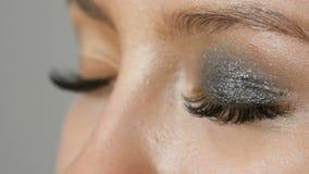 Επαγγελματική υψηλή μόδα Ο καλλιτέχνης Makeup κάνει τα πρότυπα τα καπνώδη μάτια με τη βοήθεια της ειδικής γκρίζας σκιάς ματιών, μ φιλμ μικρού μήκους