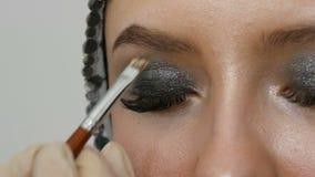 Επαγγελματική υψηλή μόδα makeup Το πρότυπο κοριτσιών σύρει τα φρύδια με μια ειδική βούρτσα φρυδιών Μοντέρνα καπνώδη μάτια απόθεμα βίντεο