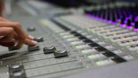 Επαγγελματικός ακουστικός αναμίκτης Ένα μικρό βάθος του τομέα, τρέμοντας λάμπες φωτός Χέρια της ακουστικής εργασίας μηχανικών Υγι απόθεμα βίντεο
