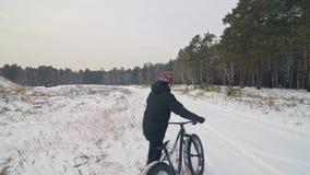 Επαγγελματικός ακραίος περίπατος ποδηλατών αθλητικών τύπων με το παχύ ποδήλατο υπαίθρια Το περπάτημα ποδηλατών στο δασικό άτομο χ φιλμ μικρού μήκους