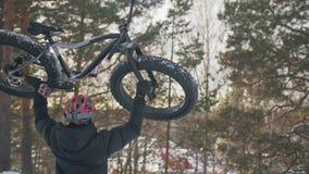 Επαγγελματικός ακραίος ποδηλάτης αθλητικών τύπων για να αντέξει το παχύ ποδήλατο στο επάνω βουνό σε υπαίθριο Περίπατος ποδηλατών  φιλμ μικρού μήκους