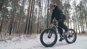 Επαγγελματικός ακραίος ποδηλάτης αθλητικών τύπων που οδηγά ένα παχύ ποδήλατο υπαίθρια Ο γύρος ποδηλατών στο δασικό άτομο χειμεριν φιλμ μικρού μήκους