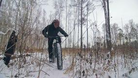 Επαγγελματικός ακραίος ποδηλάτης αθλητικών τύπων που οδηγά ένα παχύ ποδήλατο υπαίθρια Ο γύρος ποδηλατών στο δασικό άτομο χειμεριν απόθεμα βίντεο