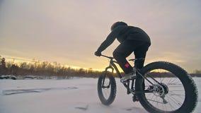 Επαγγελματικός ακραίος ποδηλάτης αθλητικών τύπων που οδηγά ένα παχύ ποδήλατο υπαίθρια Γύρος ποδηλατών το χειμώνα στον πάγο χιονιο φιλμ μικρού μήκους