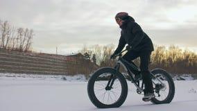 Επαγγελματικός ακραίος ποδηλάτης αθλητικών τύπων που οδηγά ένα παχύ ποδήλατο υπαίθρια Γύρος ποδηλατών το χειμώνα στον πάγο χιονιο απόθεμα βίντεο