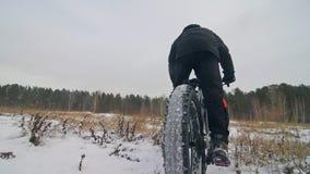 Επαγγελματικός ακραίος ποδηλάτης αθλητικών τύπων που οδηγά το παχύ ποδήλατο υπαίθρια Ο γύρος ποδηλατών το χειμώνα στον τομέα χιον απόθεμα βίντεο