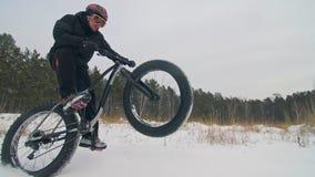 Επαγγελματικός ακραίος ποδηλάτης αθλητικών τύπων που οδηγά το παχύ ποδήλατο σε υπαίθριο Ο γύρος ποδηλατών στο δασικό άτομο χειμερ φιλμ μικρού μήκους