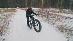 Επαγγελματικός ακραίος ποδηλάτης αθλητικών τύπων που οδηγά το παχύ ποδήλατο σε υπαίθριο Ο γύρος ποδηλατών στο δασικό άτομο χειμερ απόθεμα βίντεο