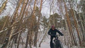 Επαγγελματικός ακραίος ποδηλάτης αθλητικών τύπων που οδηγά το παχύ ποδήλατο υπαίθρια Ύφος προς τα κάτω Γύρος ποδηλατών το χειμώνα απόθεμα βίντεο