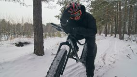 Επαγγελματικός ακραίος ποδηλάτης αθλητικών τύπων που οδηγά το παχύ ποδήλατο υπαίθρια Ο γύρος ποδηλατών το χειμώνα στον τομέα χιον φιλμ μικρού μήκους