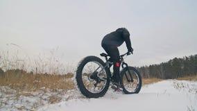 Επαγγελματικός ακραίος ποδηλάτης αθλητικών τύπων που οδηγά το παχύ ποδήλατο σε υπαίθριο Άποψη κινηματογραφήσεων σε πρώτο πλάνο τη απόθεμα βίντεο