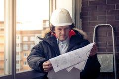 Επαγγελματικός αρσενικός επιχειρηματίας κατασκευής με τα σχεδιαγράμματά του Εστίαση, που τονίζεται μαλακή Στοκ εικόνα με δικαίωμα ελεύθερης χρήσης