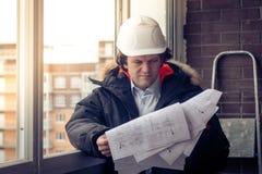 Επαγγελματικός αρσενικός επιχειρηματίας κατασκευής με τα σχεδιαγράμματά του Εστίαση, που τονίζεται μαλακή Στοκ φωτογραφία με δικαίωμα ελεύθερης χρήσης