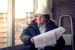 Επαγγελματικός αρσενικός επιχειρηματίας κατασκευής με τα σχεδιαγράμματά του Εστίαση, που τονίζεται μαλακή Στοκ εικόνες με δικαίωμα ελεύθερης χρήσης