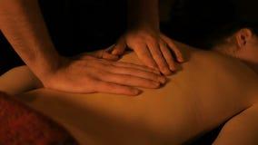 Επαγγελματικός αρσενικός μασέρ που κάνει το μασάζ για το θηλυκό πελάτη στο σαλόνι SPA φιλμ μικρού μήκους
