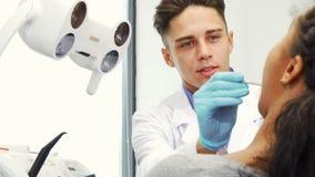 Επαγγελματικός αρσενικός οδοντίατρος που εξετάζει τα δόντια του ασθενή του απόθεμα βίντεο
