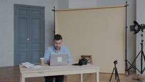 Επαγγελματικός αρσενικός όμορφος φωτογράφος που εργάζεται στο στούντιο φωτογραφιών του με το lap-top Αυτός εικόνες συνεδρίασης κα απόθεμα βίντεο