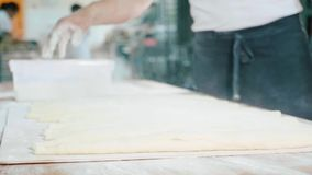Επαγγελματικός αρτοποιός που χύνει ένα αλεύρι στο ακατέργαστο ψωμί πρίν ψήνει στην κουζίνα αρτοποιείων απόθεμα βίντεο