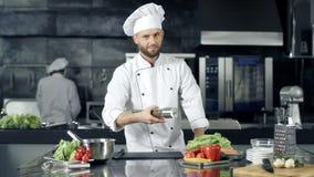 Επαγγελματικός αρχιμάγειρας που προετοιμάζεται να μαγειρεψει στην κουζίνα Αρχιμάγειρας που θερμαίνει με την πιπεριέρα απόθεμα βίντεο