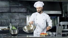 Επαγγελματικός αρχιμάγειρας που ρίχνει τα τρόφιμα στο τηγάνι με το κάψιμο της φλόγας στην κουζίνα απόθεμα βίντεο