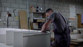 Επαγγελματικός βιομηχανικός εργάτης σε έναν ομοιόμορφο συγκεντρώνοντας έπιπλα στο εργαστήριο φιλμ μικρού μήκους