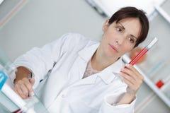 Επαγγελματικός γιατρός που κάνει τις σημειώσεις για το δείγμα αίματος στοκ φωτογραφία