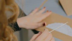 Επαγγελματικός διακοσμητής γυναικών, σχεδιαστής που εργάζεται με το έγγραφο του Κραφτ απόθεμα βίντεο