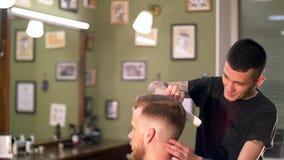 Επαγγελματικός διαστισμένος κουρέας που δίνει ένα νέο κούρεμα στον πελάτη του σε ένα barbershop φιλμ μικρού μήκους