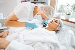 Επαγγελματικός ειδικευμένος θηλυκός δερματολόγος που χρησιμοποιεί ένα dermoscope στοκ εικόνα με δικαίωμα ελεύθερης χρήσης
