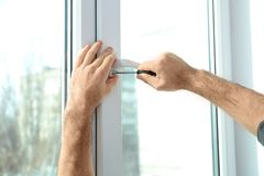 Επαγγελματικός εργάτης οικοδομών που εγκαθιστά το παράθυρο στο εσωτερικό στοκ φωτογραφία