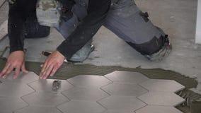 Επαγγελματικός εργαζόμενος που βάζει τα hexagon μαζικά κεραμίδια πετρών στο πάτωμα απόθεμα βίντεο