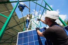 Επαγγελματικός εργαζόμενος που εγκαθιστά τα ηλιακά πλαίσια στην πράσινη κατασκευή μετάλλων στοκ εικόνα