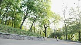 Επαγγελματικός ισχυρός μεμβρανοειδής αναβάτης ποδηλάτων που κατεβαίνει στο curvy δρόμο που φορά το μαύρα Τζέρσεϋ και τα σορτς Ποδ απόθεμα βίντεο