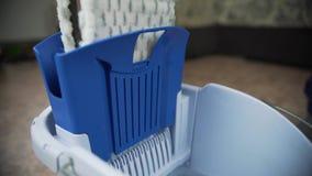 Επαγγελματικός καθαρισμός πατωμάτων με ένα MOP Ένα άτομο από την καθαρίζοντας επιχείρηση πλένει το πάτωμα στο καθιστικό φιλμ μικρού μήκους