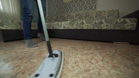 Επαγγελματικός καθαρισμός πατωμάτων με ένα MOP Ένα άτομο από την καθαρίζοντας επιχείρηση πλένει το πάτωμα στο καθιστικό απόθεμα βίντεο