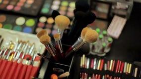 Επαγγελματικός καλλιτέχνης καλλυντικών makeup στον πίνακα Πολύχρωμο κραγιόν, σκιές και ποικίλες καλλυντικές βούρτσες φιλμ μικρού μήκους