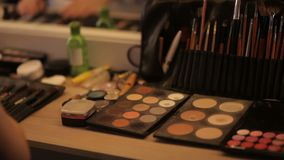 Επαγγελματικός καλλιτέχνης καλλυντικών makeup στον πίνακα στο στούντιο Πολύχρωμο κραγιόν, σκιές, μια βάση σε μια σύνθεση φιλμ μικρού μήκους