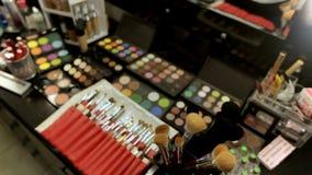 Επαγγελματικός καλλιτέχνης καλλυντικών makeup στον πίνακα στο στούντιο Πολύχρωμο κραγιόν, σκιές και ποικίλος απόθεμα βίντεο