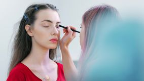 Επαγγελματικός καλλιτέχνης σύνθεσης που βάζει τον ελαφρύ εγχυτήρα για το βλέφαρο του νέου ευρωπαϊκού πελάτη γυναικών απόθεμα βίντεο