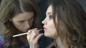Επαγγελματικός καλλιτέχνης σύνθεσης που εφαρμόζει το φωτεινό κόκκινο κραγιόν στο όμορφο κορίτσι που χρησιμοποιεί την ειδική χειλι απόθεμα βίντεο