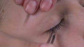 Επαγγελματικός καλλιτέχνης σύνθεσης που εφαρμόζει eyelash την επέκταση, που προετοιμάζεται για το γεγονός φιλμ μικρού μήκους