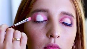 Επαγγελματικός καλλιτέχνης σύνθεσης που κάνει το όμορφο κορίτσι makeup απόθεμα βίντεο
